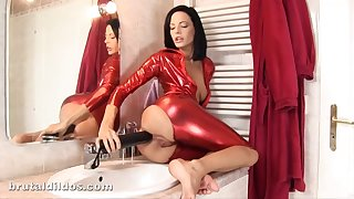 Lusty brunette forth red spandex costume is indoctrination her penurious aggravation hole with a massive mating toy